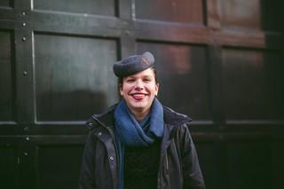 Vrouw met baret voor deur