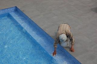 Schoonmaker maakt het zwembad schoon.