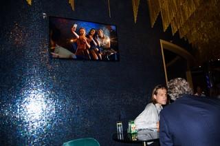 Tim met op de achtergrond een tv waarop vrouwen een foto van zichzelf maken.