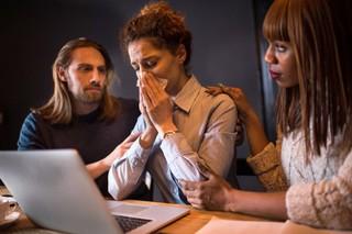 Drie geëmotioneerden achter laptop