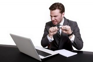 Gefrustreerde man achter laptop