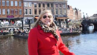 Vrouw met rode jas, tijgerprint sjaal en piloten zonnebril