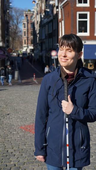 Slechtziende vrouw met blindegeleidestok en jas aan op een plein