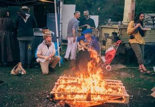 Mensen maken muziek bij kampvuur