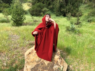 The author crouching on a rock in a red cape