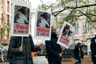 Demonstranten halten Schilder mit Kinderfotos hoch