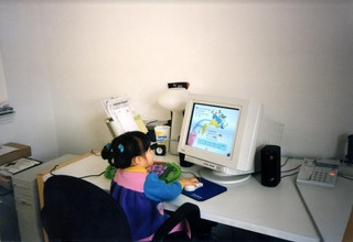 Childhood photo of writer sitting at desk playing computer games