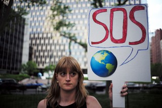 A climate protester holding up a sign.