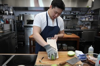 chef lucas sin of junzi kitchen cutting chayote on a mandolin