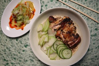 a plate of spicy chayote salad to the left of a bowl of noodles in sesame furu sauce, topped with seared chicken thighs, chayote, and cucumber