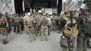 Männer in Tarnuniform vor einer Bühne