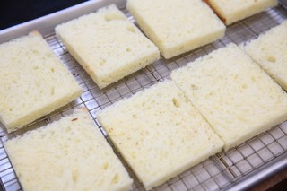 slices of white bread with the crusts cut off on a rack on a baking sheet