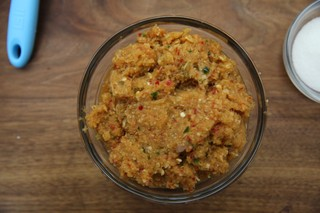 a bowl of curry paste with chiles, lemongrass, onions, shallots, and ginger in a glass bowl