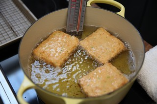 chef mei lin's shrimp toast frying in a yellow dutch oven full of oil
