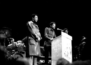 Bobby Seale speaks on a stage surrounded by bodyguards and musical equipment.