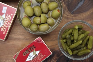cans of ortiz ventresca tuna, a bowl of green olives with pimento, and a bowl of cornichons