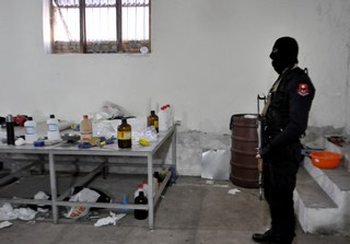 A masked Albanian police officer searches a clandestine cocaine refining laboratory in 2015.