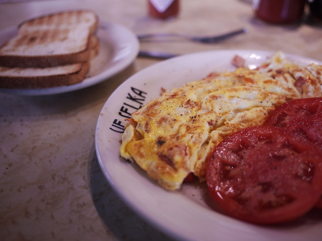 in the foreground, a plate of eggs and tomatoes at veselka in new york city; in the background, a plate of toast
