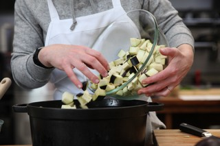 chef abra berens of granor farm and author of the book ruffage dropping diced eggplant into a dutch oven