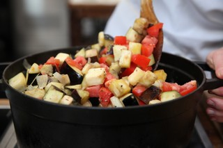 chef abra berens of granor farm and author of the book ruffage stirring up tomatoes and eggplant in a dutch oven