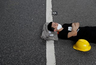 A protester, who camped out overnight, sleeps along a road near the Legislative Council building, amidst demonstrations against the extradition bill.