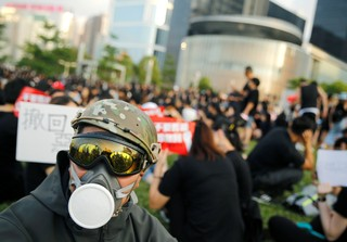A protester wearing a helmet and mask sits in front of the Legislative Council building during demonstrations.