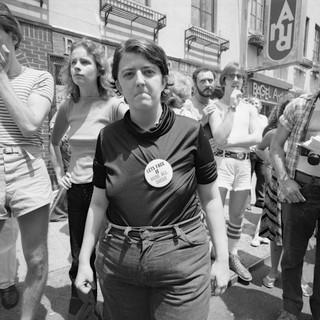 1561495531639-1977_06_PrideMarchNYC_woman_bigButton