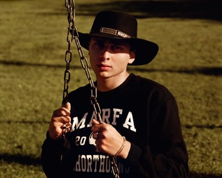 Blondey in a cowboy hat and on the playground swings