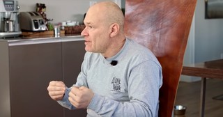 Uwe Boll looking cheerful and slightly punchy while wearing a pale gray Alone in the Dark sweater and explaining something to a figure off camera.