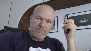 Uwe Boll looking supercilious while holding a folded pair of glasses and glaring down at the camera.