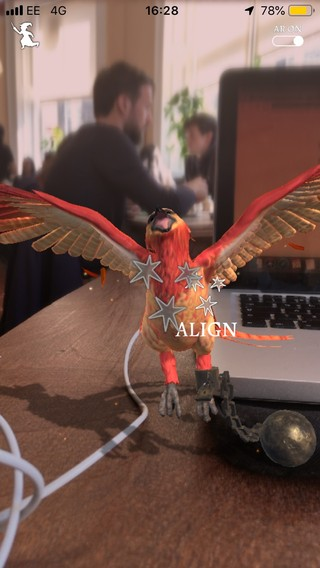 A tiny phoenix stretches its wings in Wizards Unite while in the background people sit in a cafe, going about their day.