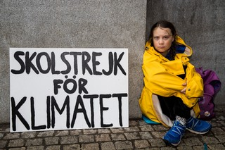 Greta Thunberg sitting on the ground next to a protest sign
