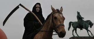 A protester dressed as Death on a horse.