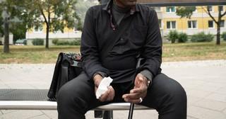 Ein Mann sitzt auf der Bank an der Bushaltestelle