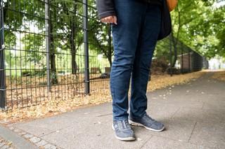 Füße und Beine einer Frau vor einem Zaun