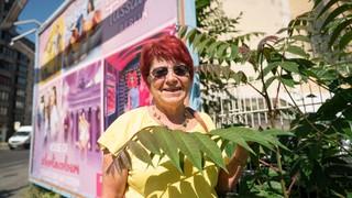 Eine Frau mit roten Haaren steht vor einer Wand