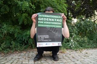 Andreas mit dem Poster für den Internationalen Gedenktag für Verstorbene Drogengebraucher*innen