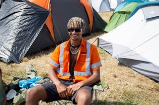 Ein Mann in Warnweste sitzt auch einem Campingstuhl