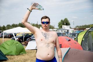 Ein Mann auf einem Festival schüttet sich Wasser über seinen nackten Oberkörper