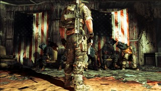 A row of black-hooded prisoners sit dead, their arms tied behind their backs to their chairs, before bloody and torn American flags in a grim scene from Spec Ops The Line
