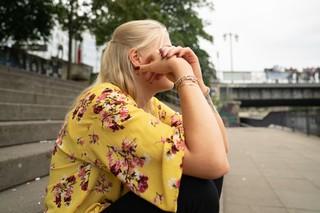 eine blonde frau sitzt auf einer treppe