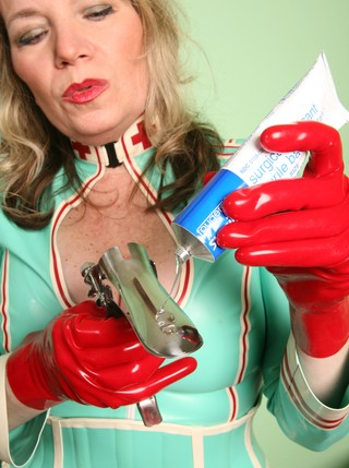 Woman dressed as nurse squirts lube onto speculum as part of gyno fetish