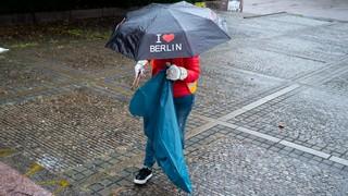 Eine Person trägt einen Regenschirm und sammelt Müll