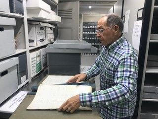Tony Cucchiara opens a chronology book at the Green-Wood Cemetery archives. Taken by Caroline Haskins.