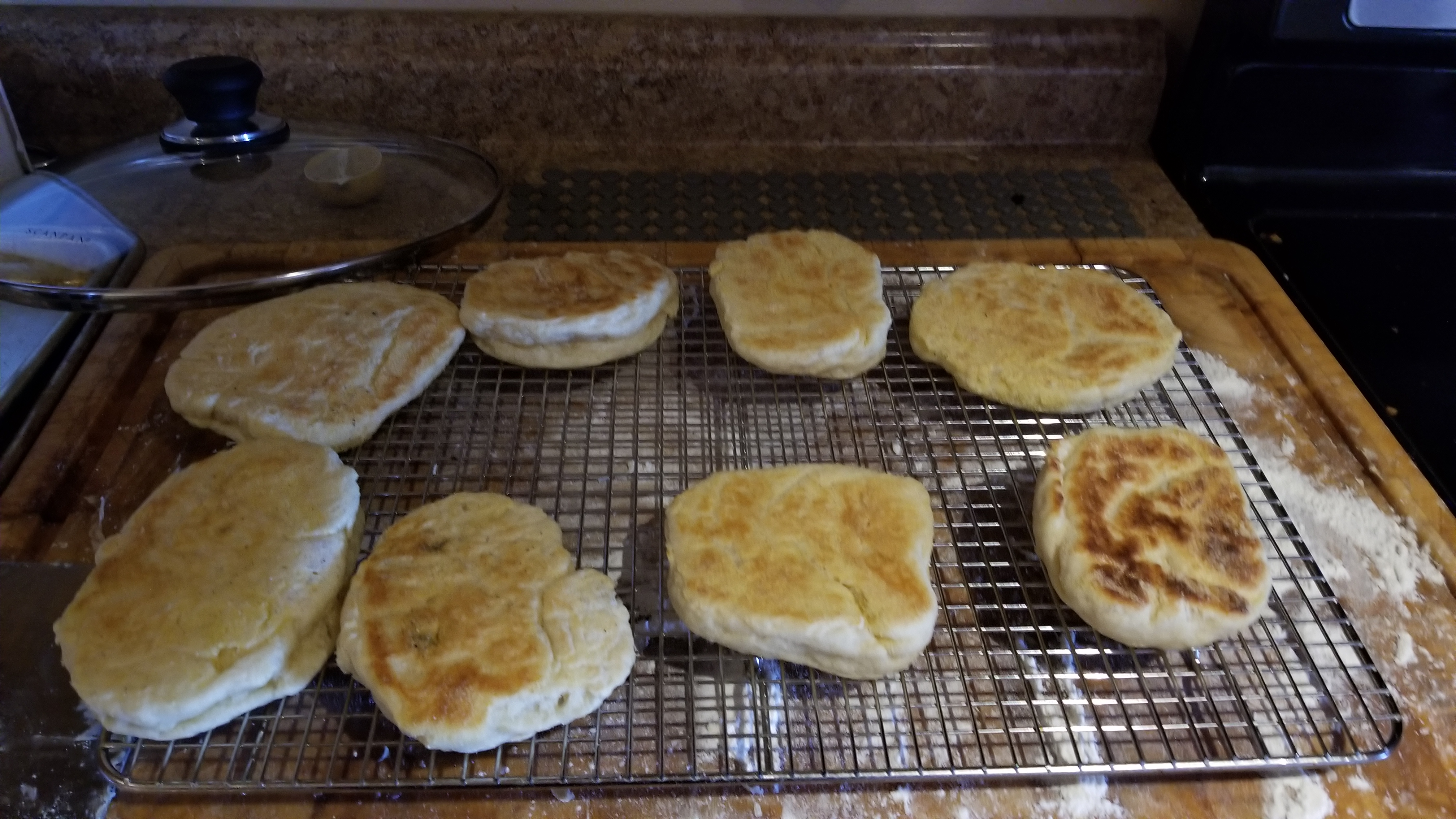 a photo of a series of flat failed english muffins on a cooling rack.