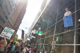A young climate protester climbs some scaffolding above a crowd.