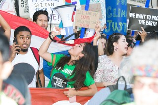A young climate protester holds a megaphone.