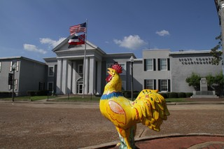 A chicken statue in front of a courthouse flying the Mississippi state flag.