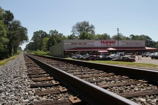 A grocery store next to train tracks.