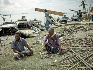 Moinul and Haidar Ali sit on the riverbank of Bhangnamari Char as the bamboo wreckage of their local school, built in 1948, is loaded onto ships for sale in the mainland. The school was destroyed during intense flooding in July.